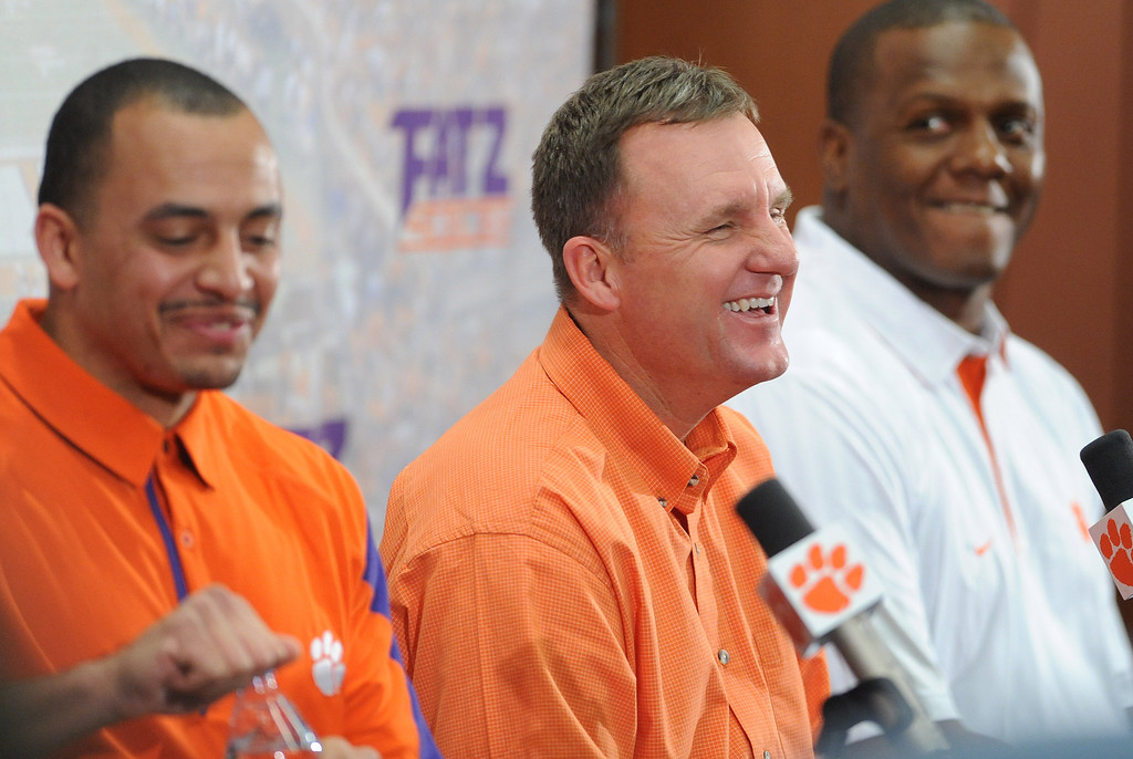 New Clemson offensive coordinator Chad Morris answers questions during a press conference in the WestZone where he, along with running backs coach Tony Elliott, left, and defensive ends coach Marion Hobby, right, were introduced Thursday, January 13, 2011. BART BOATWRIGHT/Staff