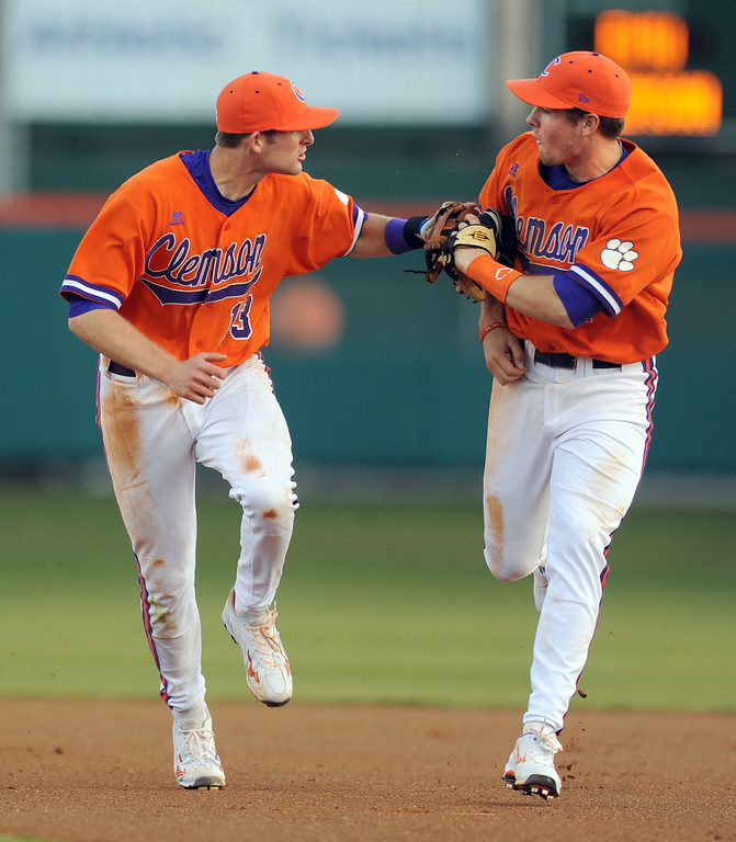 Clemson short stop Brad Miller (13), left, celebrates with second baseman Jason Stolz (2) after the two connected on the front end of a double play to end the top of the 6th inning against Eastern Michigan Friday, February 18, 2011 at Clemson's Doug Kingsmore Stadium. BART BOATWRIGHT/Staff