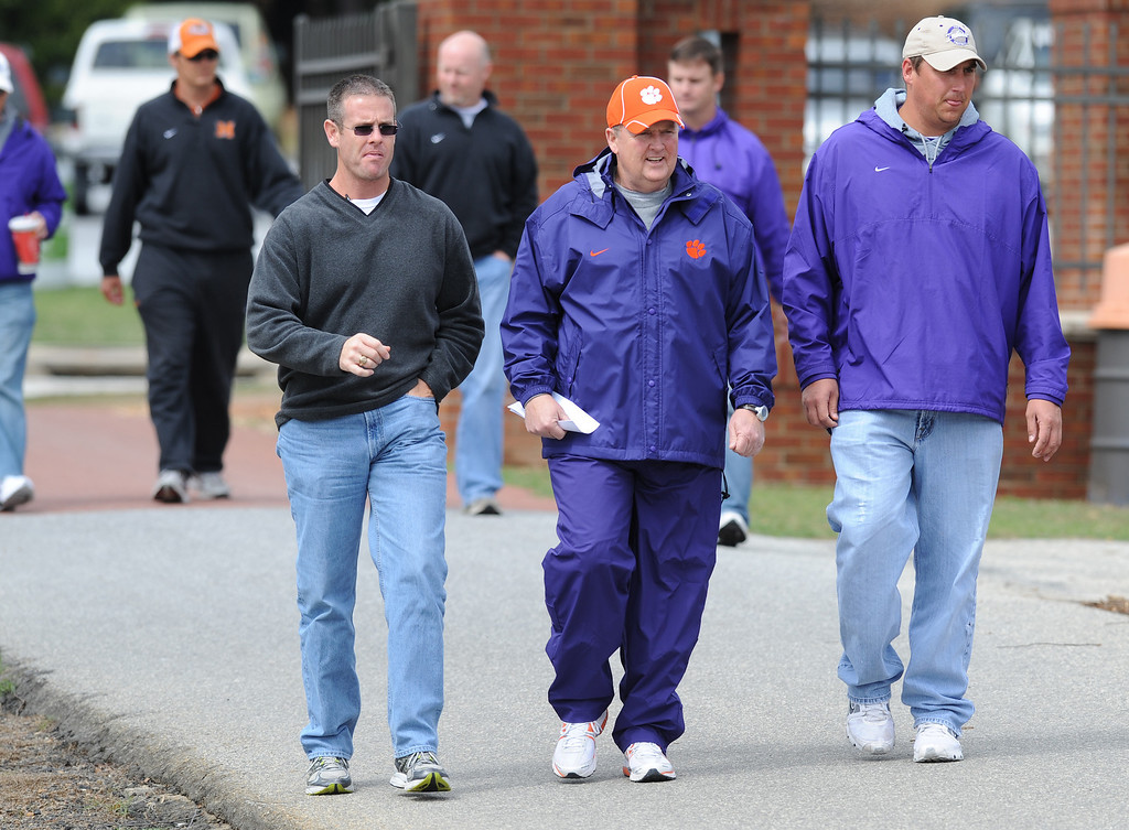 Clemson offensive line coach Robbie Caldwell, center, walks to practice Monday, March 28, 2011. BART BOATWRIGHT/Staff