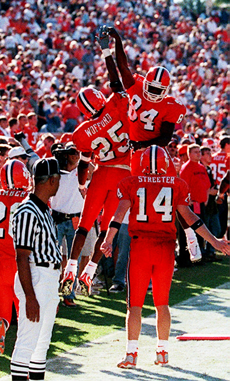 "Clemson's Brian Wofford (25) and Mal Lawyer (84) exchange ""high-fives"" on the Clemson sidelines after a touchdown. QB Brandon Streter (14) watches Saturday, November 6, 1999."