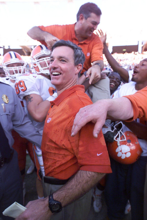 Clemson head coach Tommy Bowden smiles while assistant coach Brad Scott is carried off the field by Jason LeMay (89) and Chad Jasmin (10) after the Tigers 31-21 win over South Carolina Saturday, November 20, 1999.