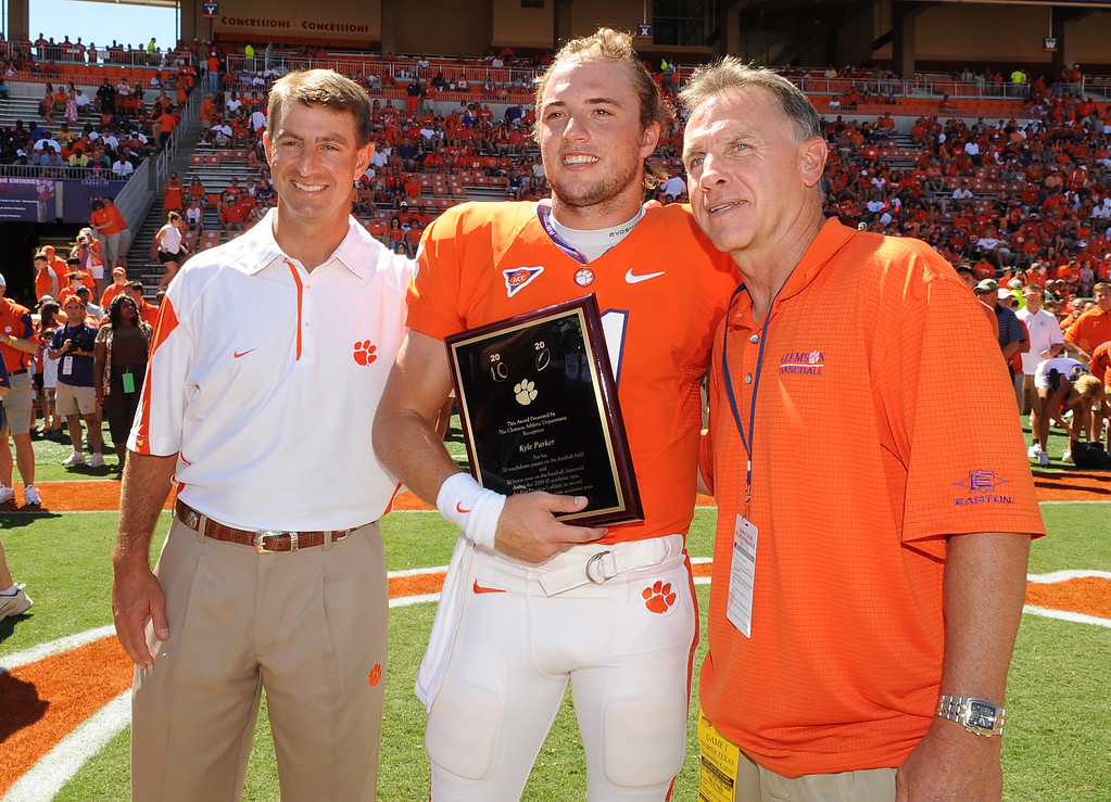 Clemson head coach Dabo Swinney, left, and head baseball coach Jack Leggett present Kyle Parker with a plaque in honor of his 20 touchdown 20 home run seasons last year  before the Tigers game against North Texas at Clemson's Memorial Stadium Saturday, September 4, 2010. Staff/Bart Boatwright